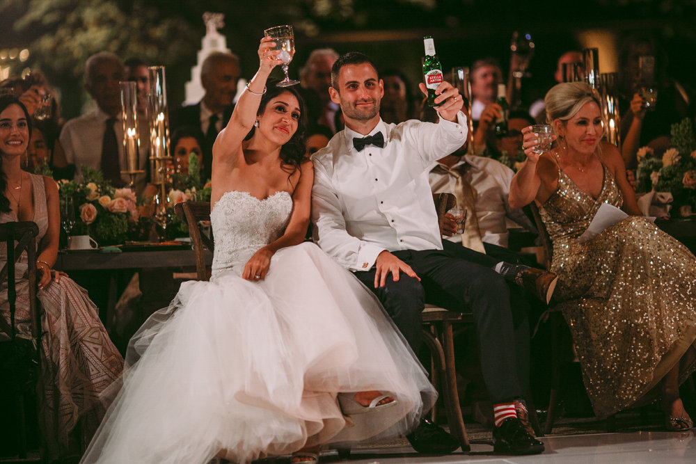 san diego wedding   photographer | married couple holding alcohol sitting down lifting a glass   and a bottle up