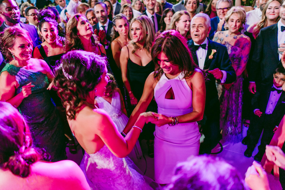san diego wedding   photographer | bride shows her wedding ring to woman in white dress in the   middle of a crowd