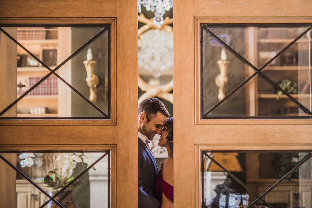 san diego wedding   photographer | woman in burgundy dress about to kiss man seen through ajar   double doors