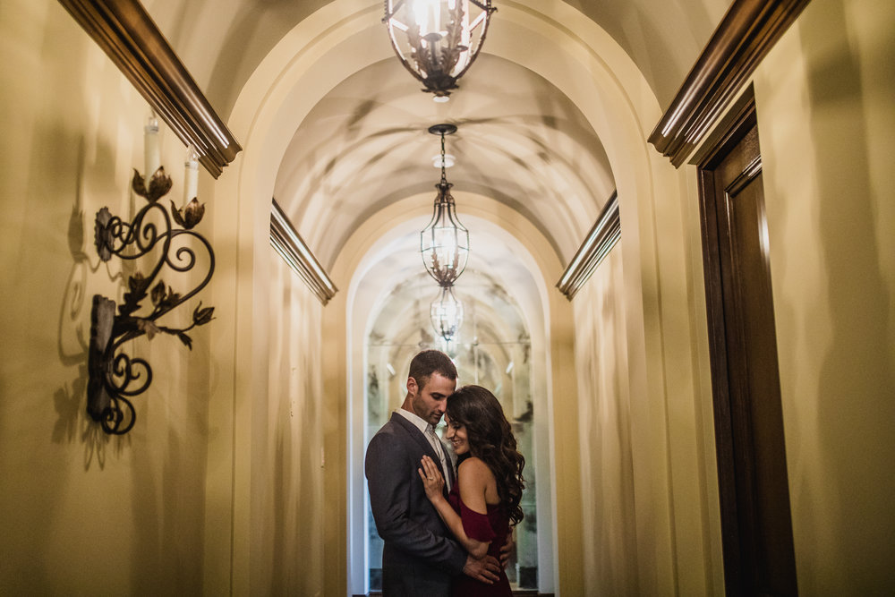 san diego wedding   photographer | couple holding each other under lighting fixture in the middle   of a hall