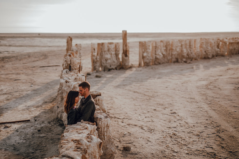 san diego wedding   photographer | couple standing between wooden fence with sand formation