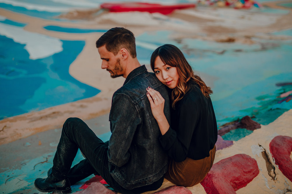 san diego wedding   photographer | couple sitting down on painted pavement while woman leans on   man's back