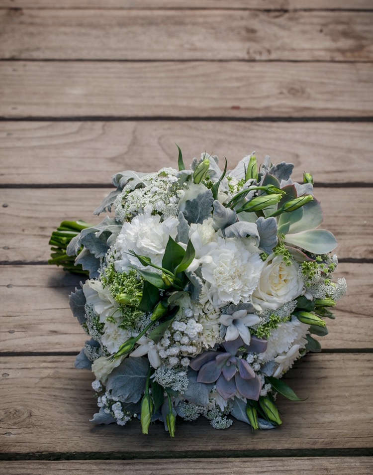 White Carnations (sweet & lovely) Baby's Breath (everlasting love) lisianthus (appreciation) succulents (cacti-ardent love) and as a surprise for the bride - stephanotis (happiness in marriage). Bouquet by Flowers by Rhi