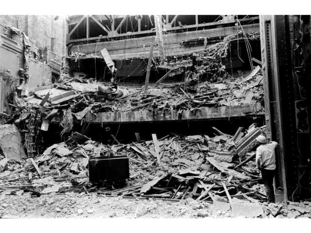 A photo of the demolition of the Pantages Theatre - with two workers taking a break on the middle ledge. Photo credit: Vancouver Public Library Archives.