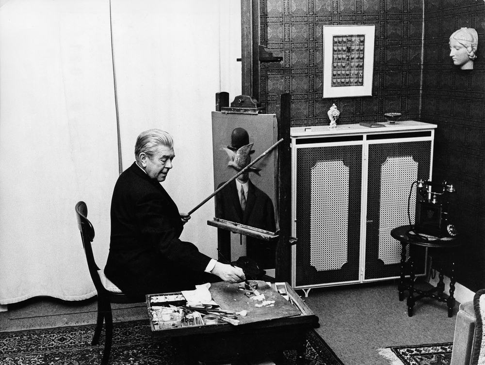 an upright René Magritte at work in their respective studios