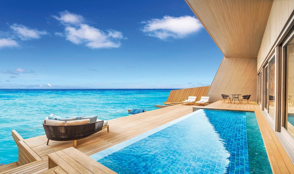 The deck of the overwater villa features a pool and endless views