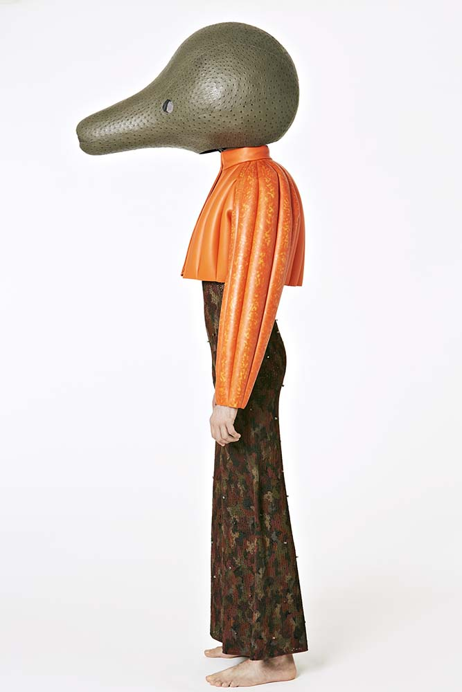 Fiber glass head covered in dark grey ostrich leather.   Orange handpainted leather bolero.   Knitted tracksuit in vegetal hand painted texture with Swarovski hand stitched stone.