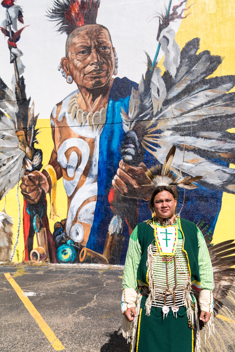 Quapaw indian poses in front of mural.