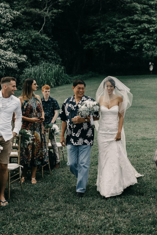 Father walking bride down the aisle at Kualoa Ranch Paliku Gardens. Photography by Hawaii wedding photographer Desiree Leilani