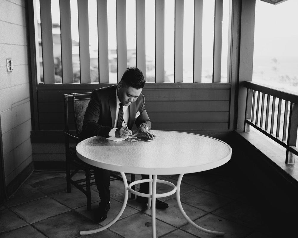 Groom writing his vows by Hawaii wedding photographer Desiree Leilani