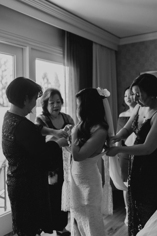 Bride getting into her wedding dress by Hawaii wedding photographer Desiree Leilani