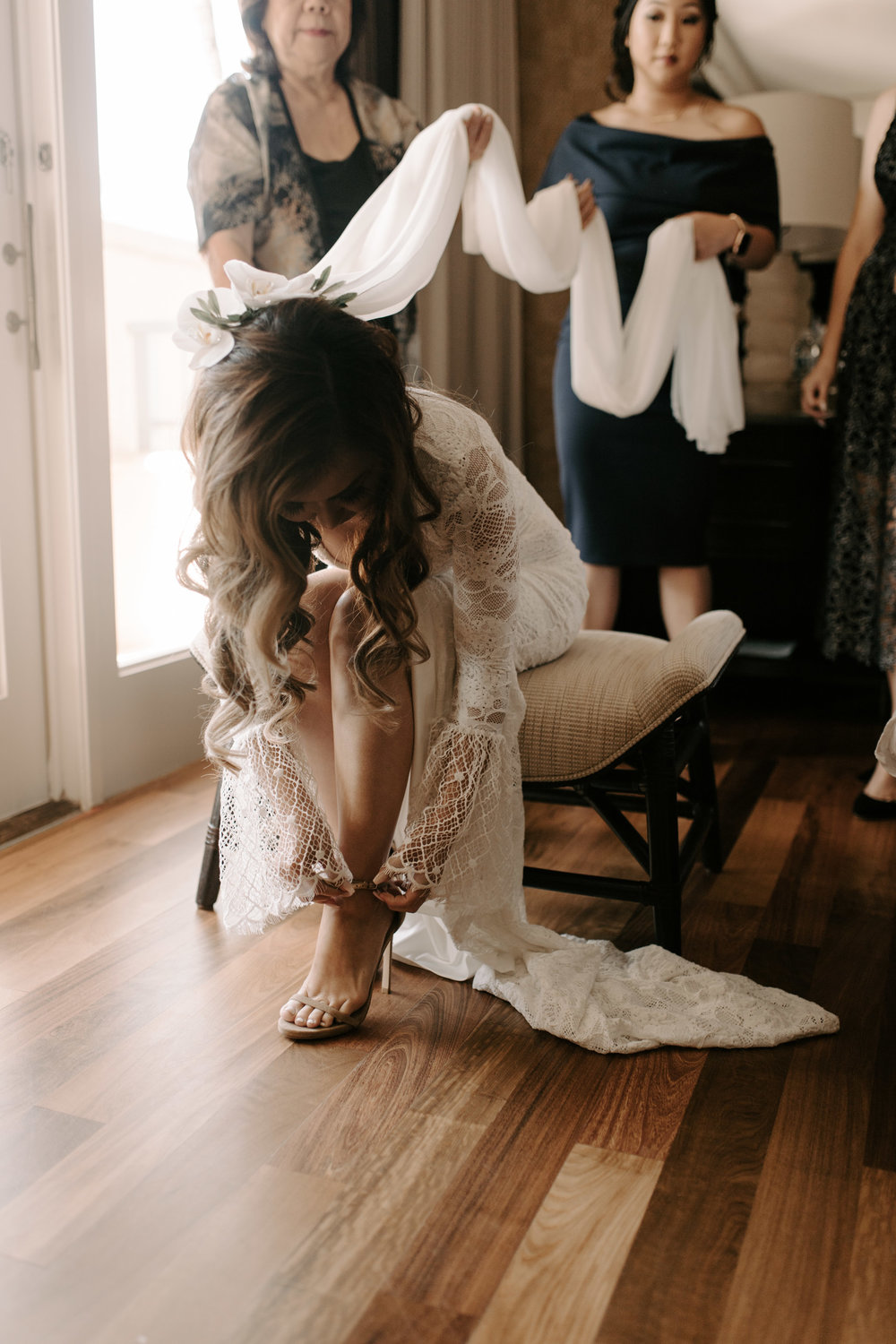 Bride putting on her shoes and getting ready at the Ritz Carlton Maui by Hawaii wedding photographer Desiree Leilani
