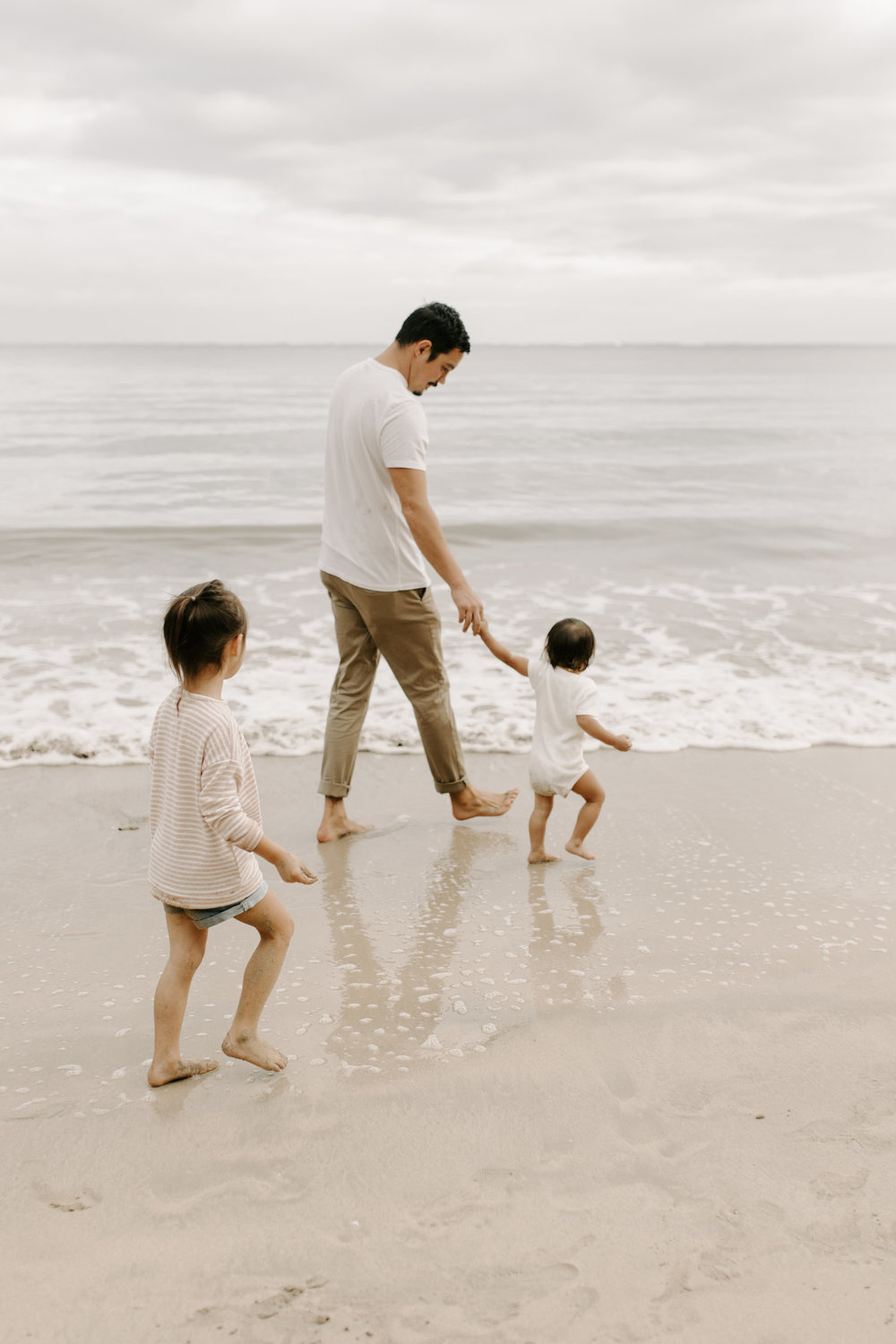 A dad and his daughters walking on the beach by Hawaii Family Photographer Desiree Leilani