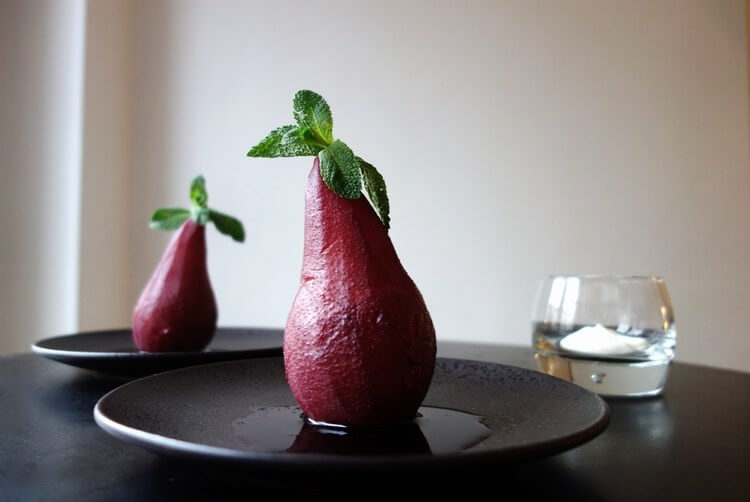 Pears poached in red wine, served with cream and garnished with fresh mint.