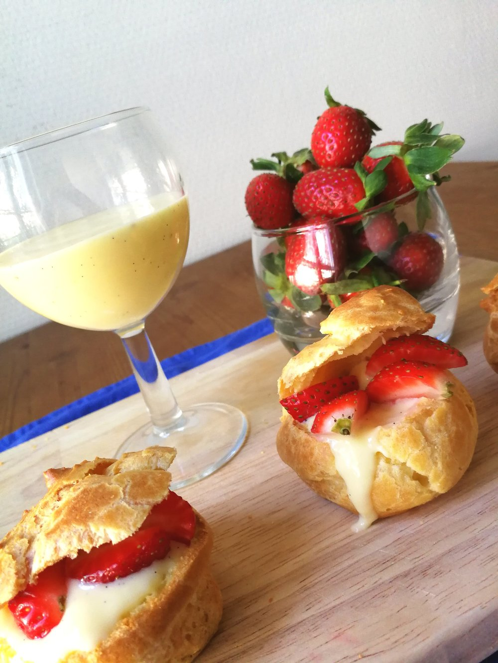 Choux - French cream puffs - served with custard and strawberries.