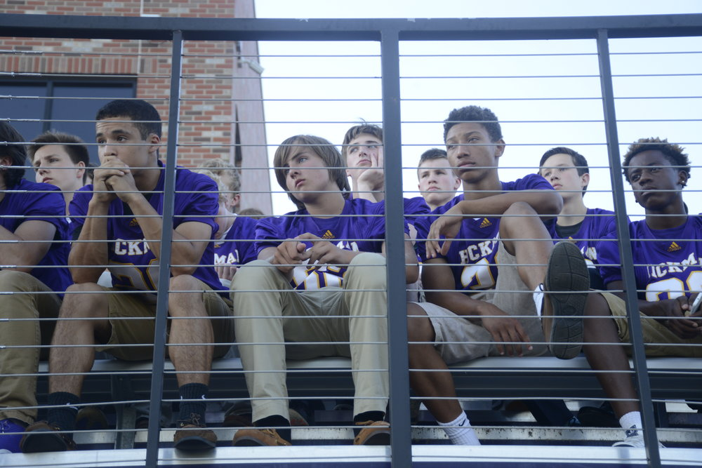 "Members of the Hickman High School football team look towards the podium during the memorial service for their late coach Arnel Monroe at Alumni Stadium. ""I was raised in foster care. Coach let me know that this was my family and that I was going to make it,"" said Damarion Avery, a Hickman senior football player."