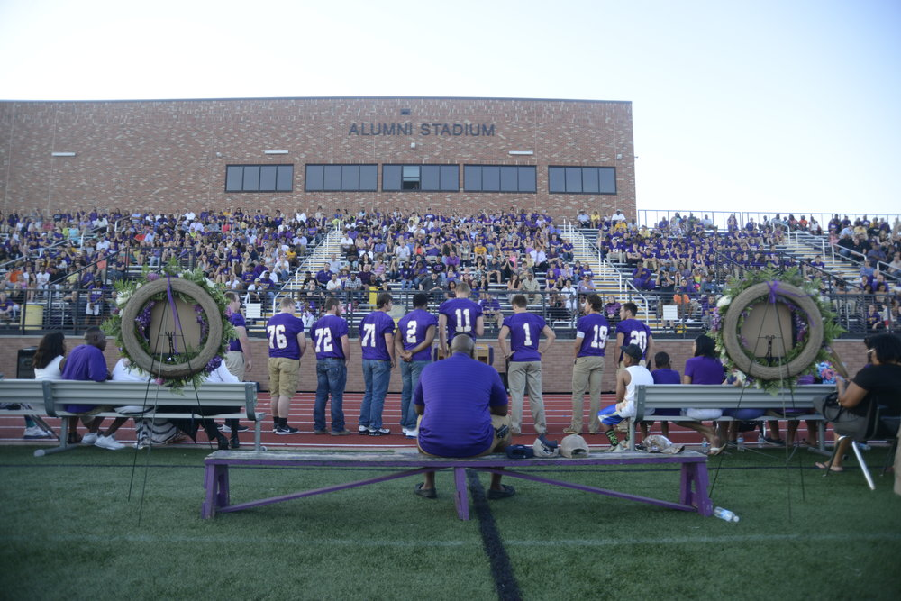 Hickman principal Eric Johnson, center, watches as the school's football players address the audience during the memorial service for Arnel Monroe at Alumni Stadium. Despite microphone issues, dozens of players, family members and friends addressed the crowd eulogizing Monroe.