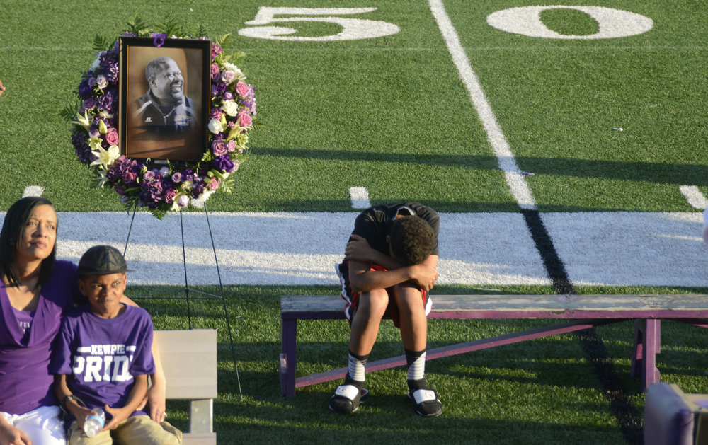 Family friend Eric Turner bows his head in mourning after giving a brief eulogy at the memorial service for Hickman High School football coach Arnel Monroe at Alumni Stadium on Thursday, June 9, 2016. Relatives, friends and former players all recounted fond memories of Monroe.
