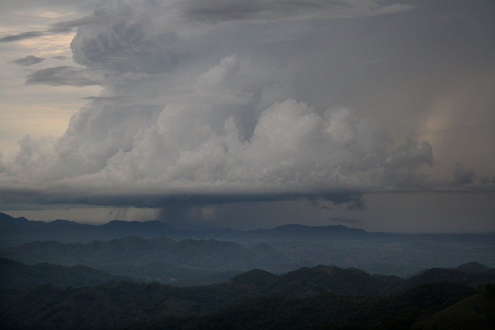 An afternoon rain showers down into the valley of Monteverde, Costa Rice. Precipitation begins to evaporate as the sun rises in the morning, frequently culminating in afternoon thunderstorms that start the water cycle over again.