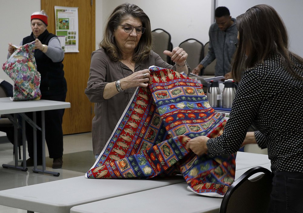 Pam Schmutzler, center, helps Colleen Meredith unfold a tablecloth for Meredith's booth at the Lincoln University Farmers' Market Friday, March 3 in Jefferson City. Schmutzler, Meredith and Mae Benson, left, were three of five vendors who came to sell their products at the market that day. The market, housed indoors during the winter, garners more vendors during the warmer months.