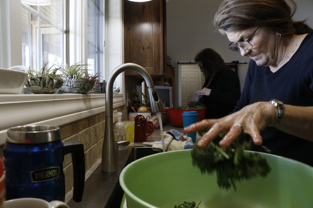 Pam Schmutzler, right, tosses freshly washed kale into a bowl while her longtime friend, Denise Redal, bags and weighs clean kale Friday, March 3 in Schmutzler's home just south of Jefferson City. Schmutzler says she sells her kale for however much she would pay for it. She charges $2 for a half-pound bag of kale and says she's interested in learning to make kale chips.