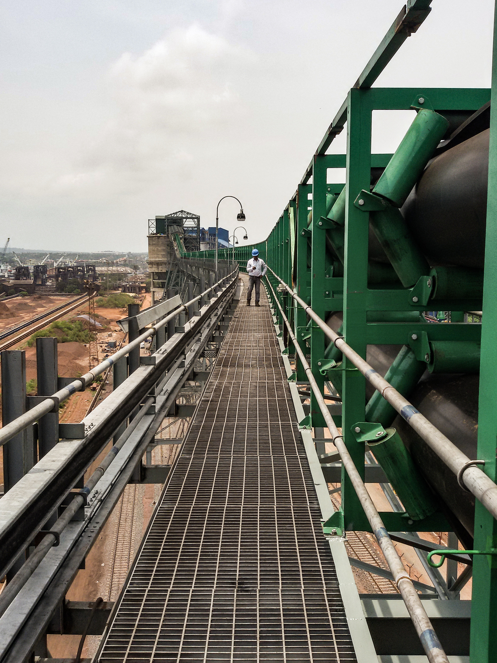 During the construction phase, a worker inspects the pipe conveyor