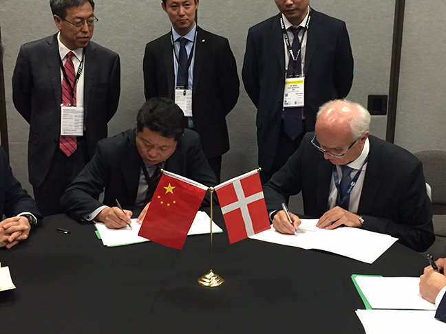 Photo:  Alongside representatives from NHI Group of China and FLSmidth, Manfred Schaffer signs the formal agreement establishing the Joint Venture between both companies.