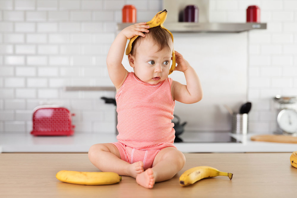 Cute baby wearing banana skin on head by Lisa Tichane, advertising kids photographer