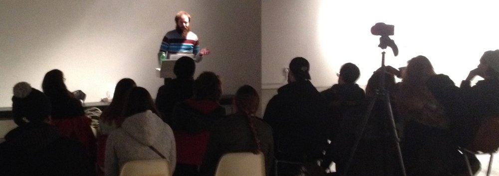 "Craig E. Ross at the ""Art and Revolution"" discussion during the Didactic Art Show (Surplus Gallery, Carbondale, 2014)"