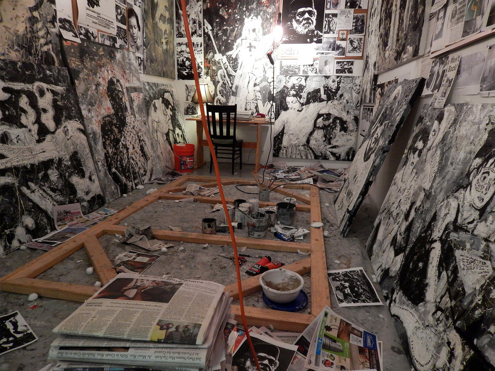 "A Painter of Our Time    (installation at the Sam Fox ""Safe Space"")   Acrylic, cotton, concrete, newspaper, ash and Sharpie on canvas with photographs, wood, newspaper, found objects, hanging lights (2014)."