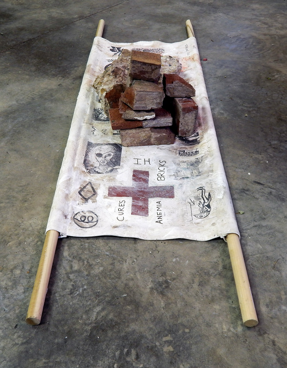 The Healing Properties of Post-Industrial Debris: IH Bricks (The Barista Who Could See the Future)    Acrylic, coffee, glitter ash, stickers, wig-hair, Sharpie on canvas with bricks from the abandoned International Harvester plant in Canton, Illinois and wood (2017).