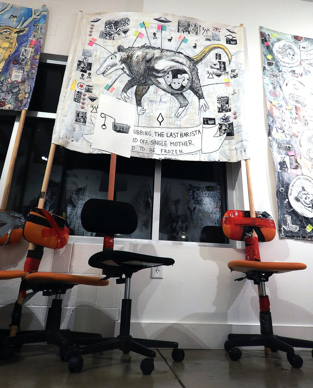 The Last Barista (Revolt of the Swivel Chairs)    Acrylic, marker, photocopies, stickers, post-it notes, buttons, coffee and mixed media on canvas banner with wood and swivel chairs (2017-2018).