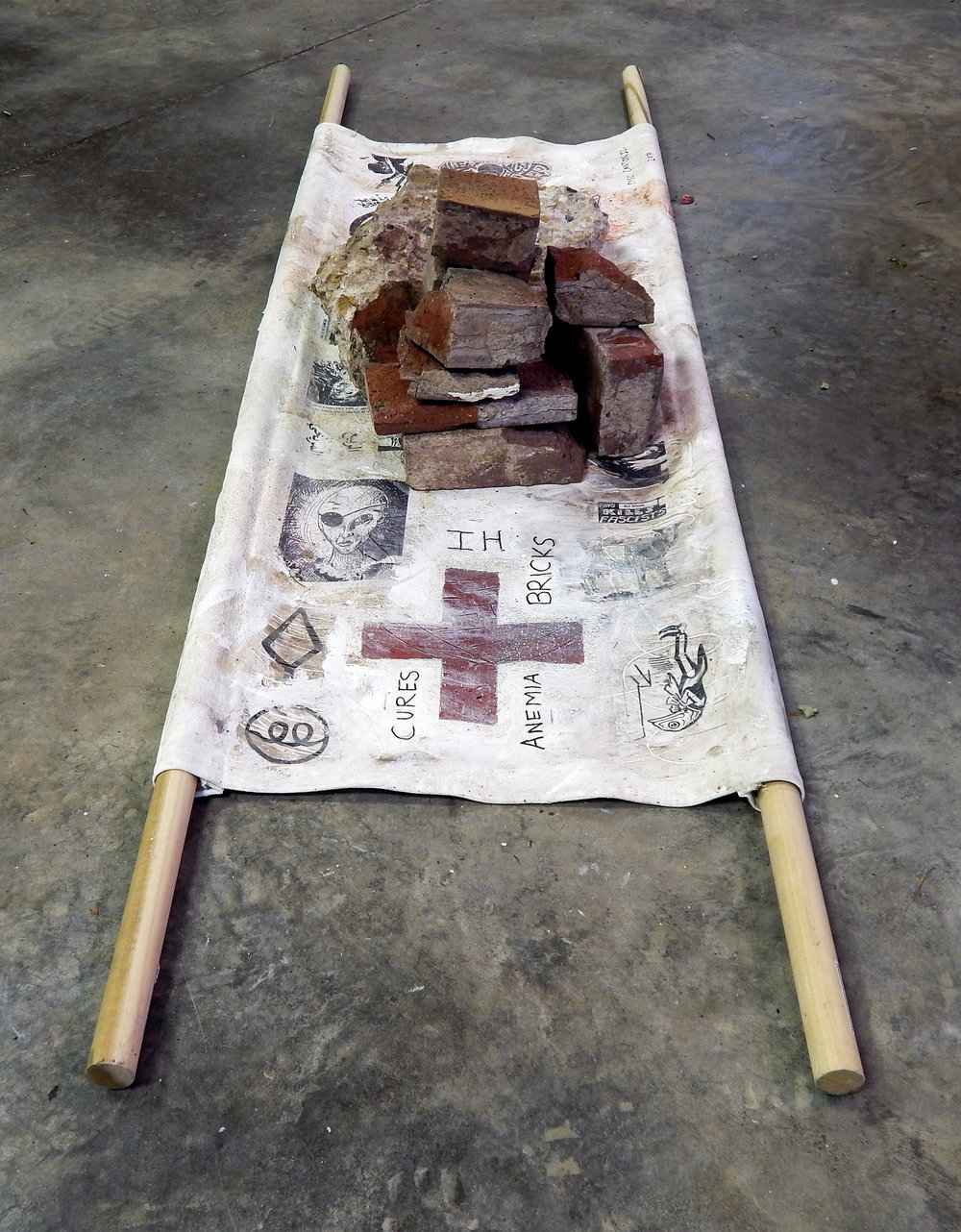 The Healing Properties of Post-Industrial Debris: IH Bricks (The Barista Who Could See the Future).   Acrylic, coffee, glitter ash, stickers, wig-hair, Sharpie on canvas with bricks from the abandoned International Harvester plant in Canton, Illinois and wood (2017). (Adam Turl)
