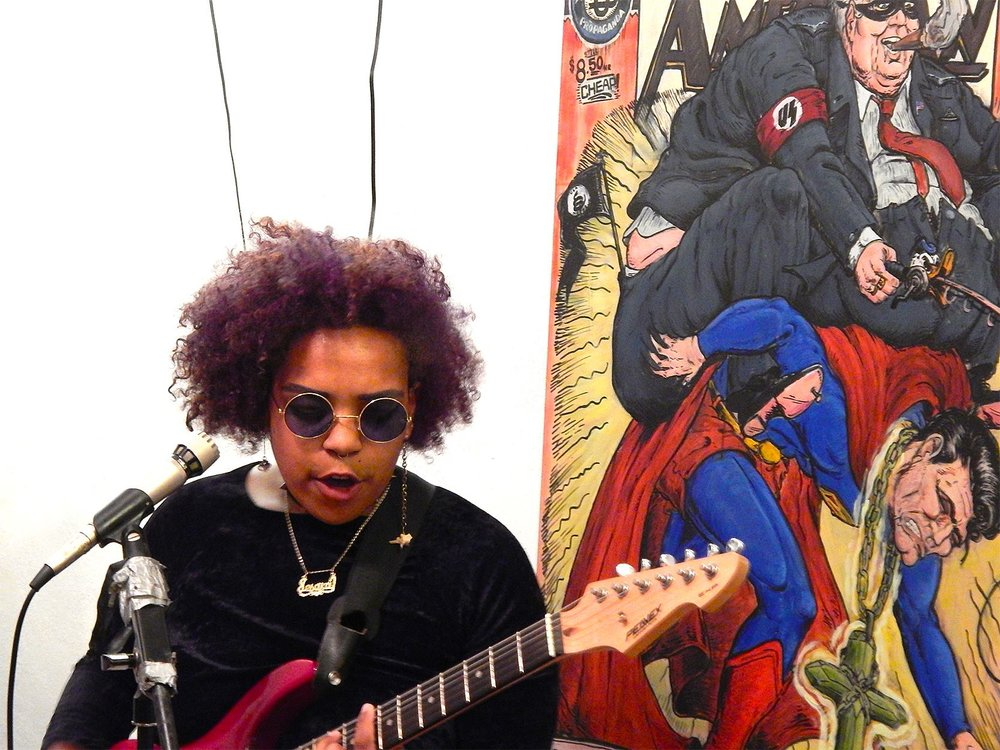 Hard Times Art Show II  with Jesa Dior Brooks at the Dollar Art House. Artwork in background by Jon Cornell. (2016)