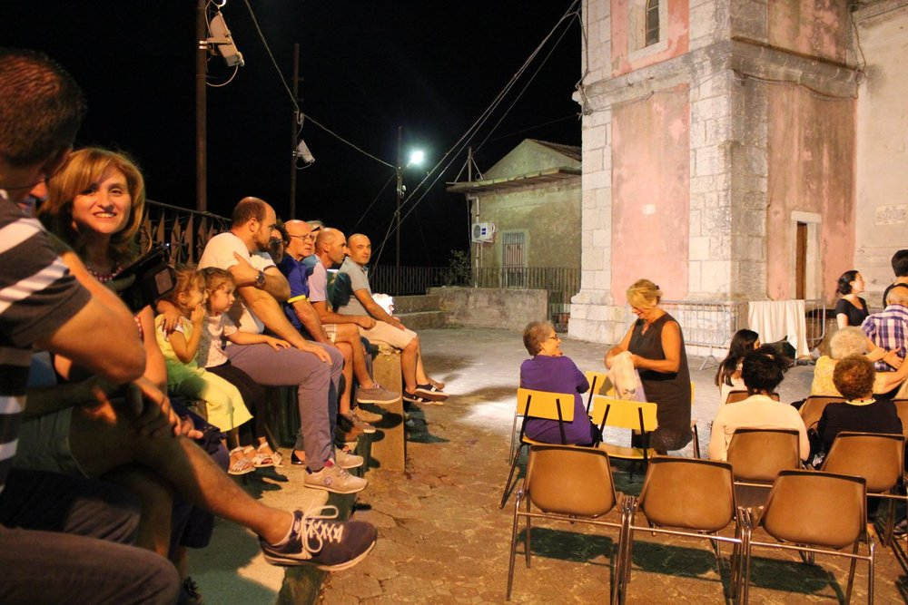 Audience members arrive for the performance in Pezzolo