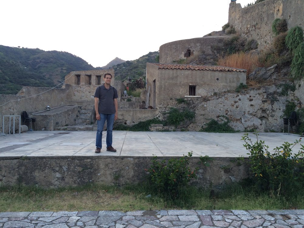 Company member Max Sklar stands on the stage at Castello Rufo Ruffo