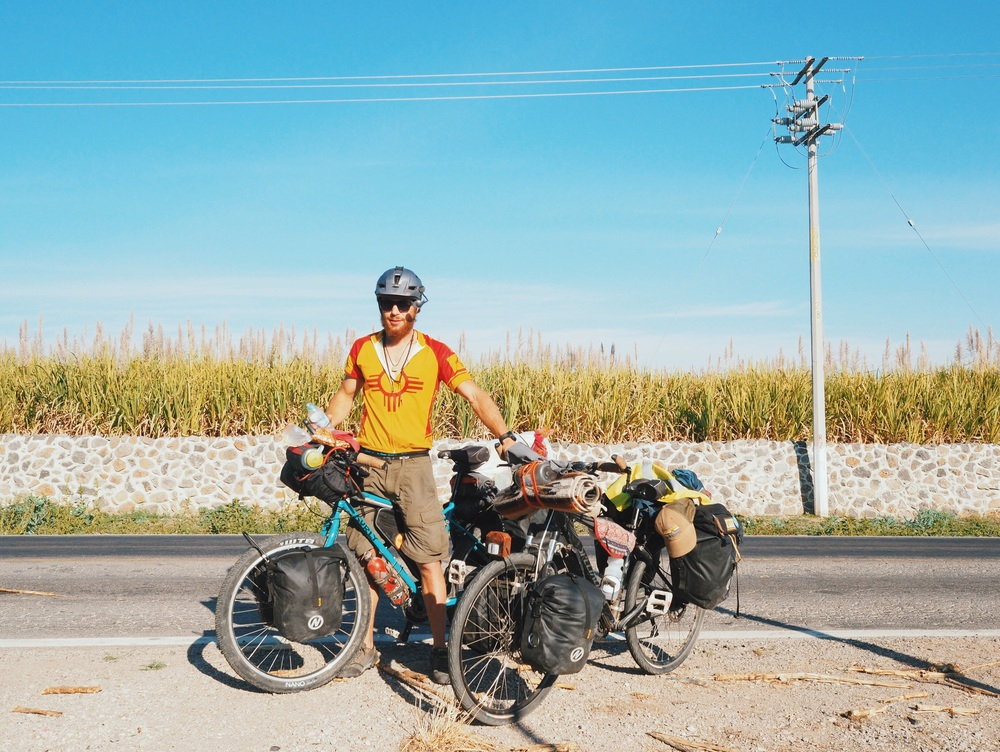 Mehedi holding Erin's bike while she takes photos on the side of the road, leaving Tuxpan