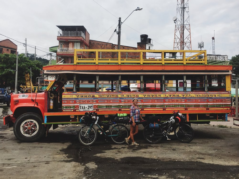 Erin with the bikes in front of a brightly-colored Colombian  chiva  bus