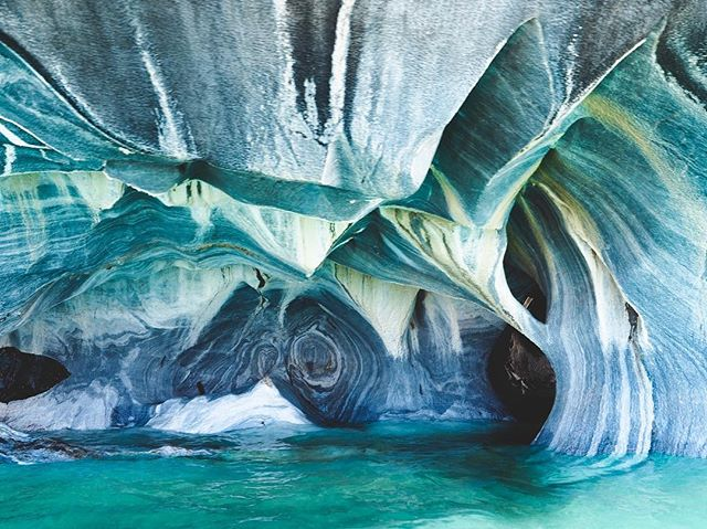 """When @chamapedal asked me in 2015 if I'd cycle to Patagonia with him, I thought to myself, """"that's where those marble caves are..."""" and my answer was a clear and emphatic yes. The marble caves are even more majestic than I ever could have imagined, being eroded in beautiful, organic patterns by Chile's largest lake (the 2nd largest lake in South America), the Lago General Carrera. We learned that iridium from melting glaciers gives the lake it's stunning color. Iridium is the least common element on our entire planet, and is found in the highest concentrations in meteorites. For this reason, it's nickname is stardust. So basically we went to a marble sculpture carved by a lake glowing from stardust. If this is a dream, please don't wake me. 🤯"""