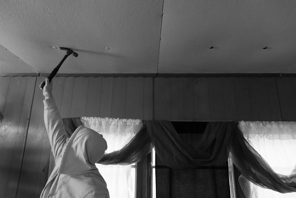 Bobby Kiser removes bottle caps from the ceiling of his trailer in Carbondale, Ohio on November 11, 2015. He has moved out so that his twin sister Becky can have a better place than her camper to prepare for the birth of her child.