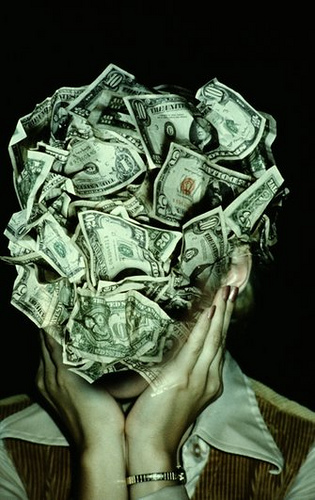 Woman Holding Head in Hands Covered in U.S. Money, Photo by Image Collection