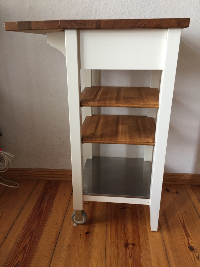 SOLD - White, Wood, and Steel Kitchen Cart – Ikea STENSTORP Servierwagen. One Drawer + 3 Shelves, Wheels on one side. Hinged and Expandable Butcher-Block Top. Has been cleaned and oiled regularly, some scratches and wear, Pre-Loved good condition. 45 x 43 x 90 cm tall. Originally €99.99 – Asking €30.