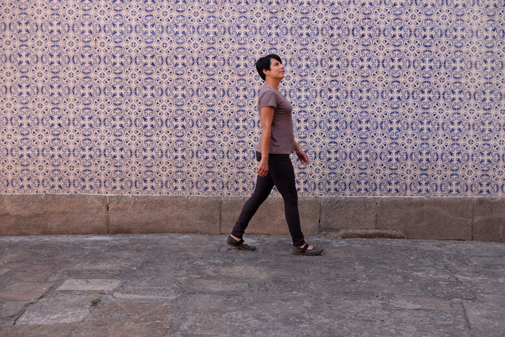 Amy walking in front of a large Portuguese tiled wall