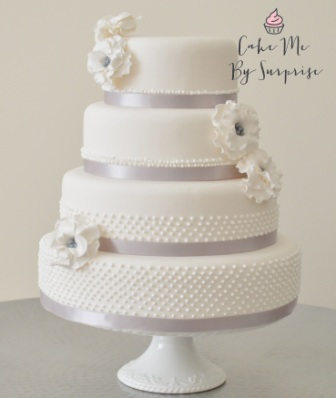 White Pearl Classic pearl embellished white wedding cake complete with ruffle flowers centered with silver beads Serves 134 £420