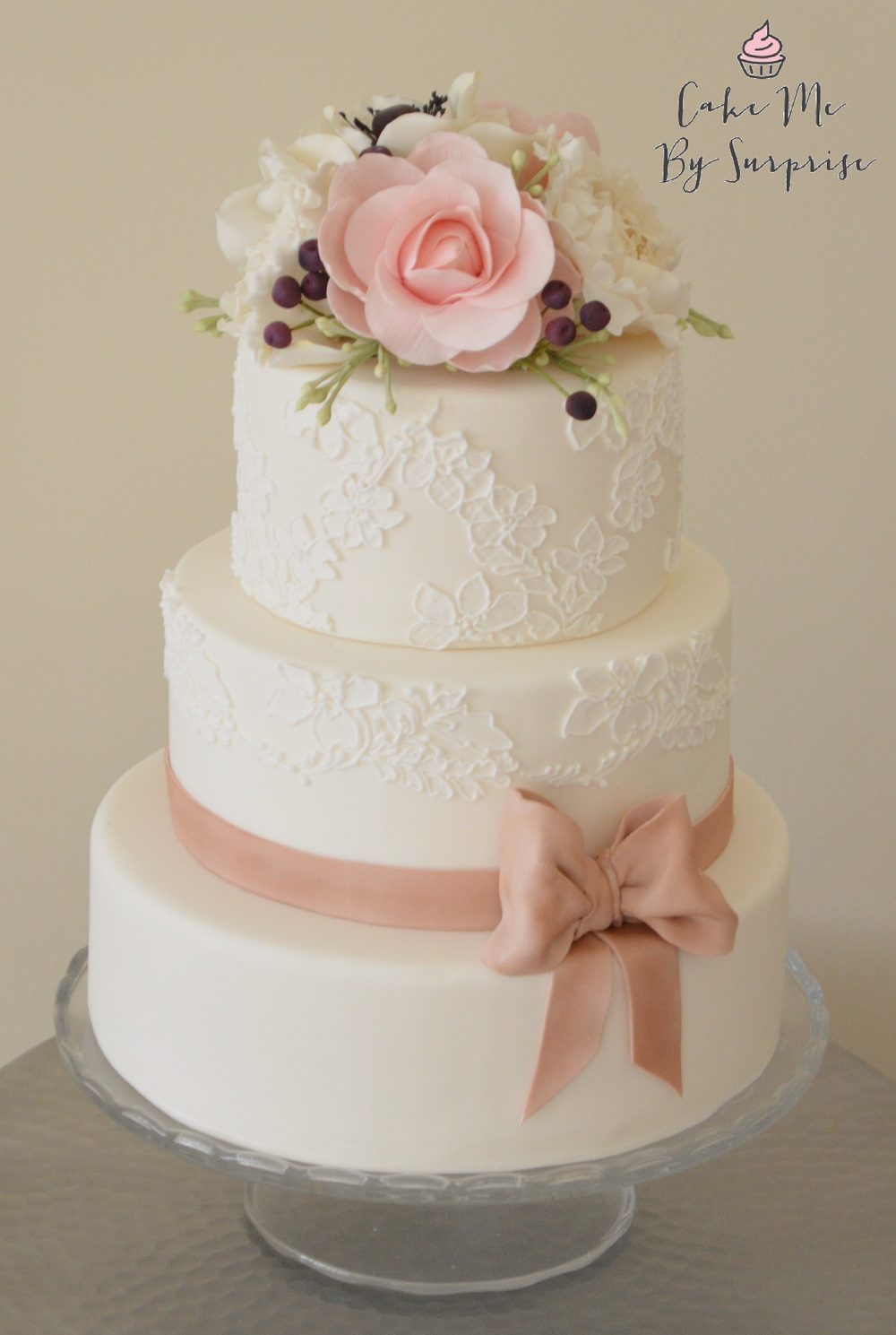 A Touch of Mink Complete your wedding celebration with this elegant cake. With its name derived from the mink colored satin ribbon that finishes this lace inspired cake. The top of the cake is finished with sugar crafted Camellias, Peonies, Anemones, Berries and Foliage.  Serves 60 £390