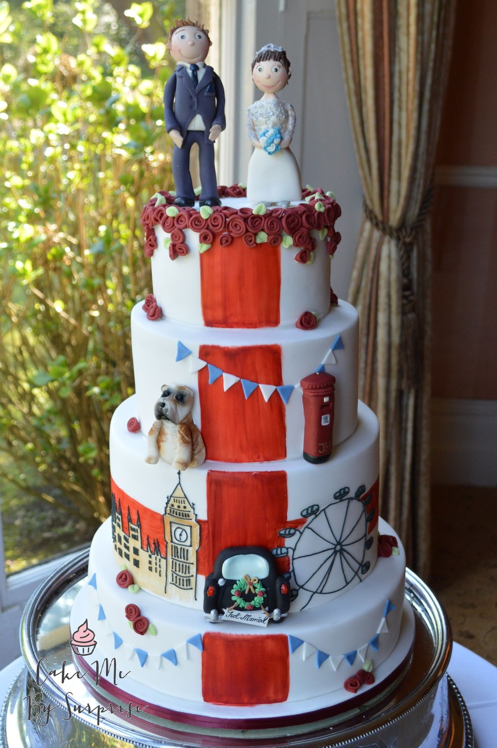 This England themed wedding cake was completed with top London attractions, such as the London eye and Big Ben. We included a British bull dog, postbox, rolled red roses and bunting.  The St Georges Flag runs down the entire cake, and to finish the design, we added a beautiful sugar crafted London taxi cab, with a swinging 'Just Married' sign and floral wreath.