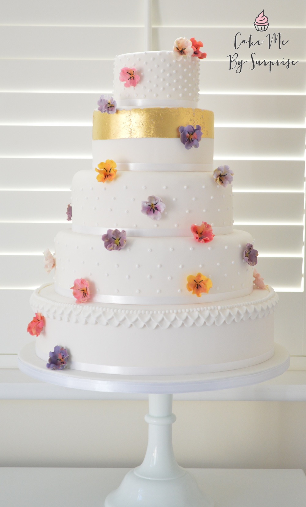 Falling Pansy A perfectly elegant wedding cake, with dotted piping, a 24ct gold metallic gold leaf band, and hand made sugar pansies in an array of beautiful colours.  Serves 145 £750