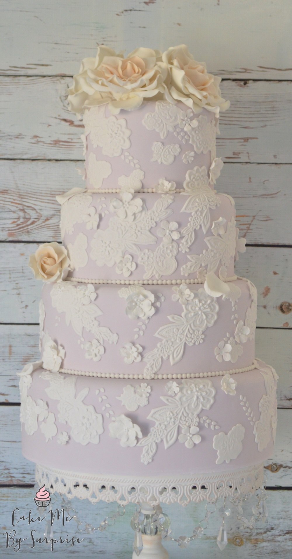 Julianne A delicate lavender wedding cake, complete with ivory centered avalanche roses, lace applique design and soft blossoms with pearl piping.  Serves 134 £740