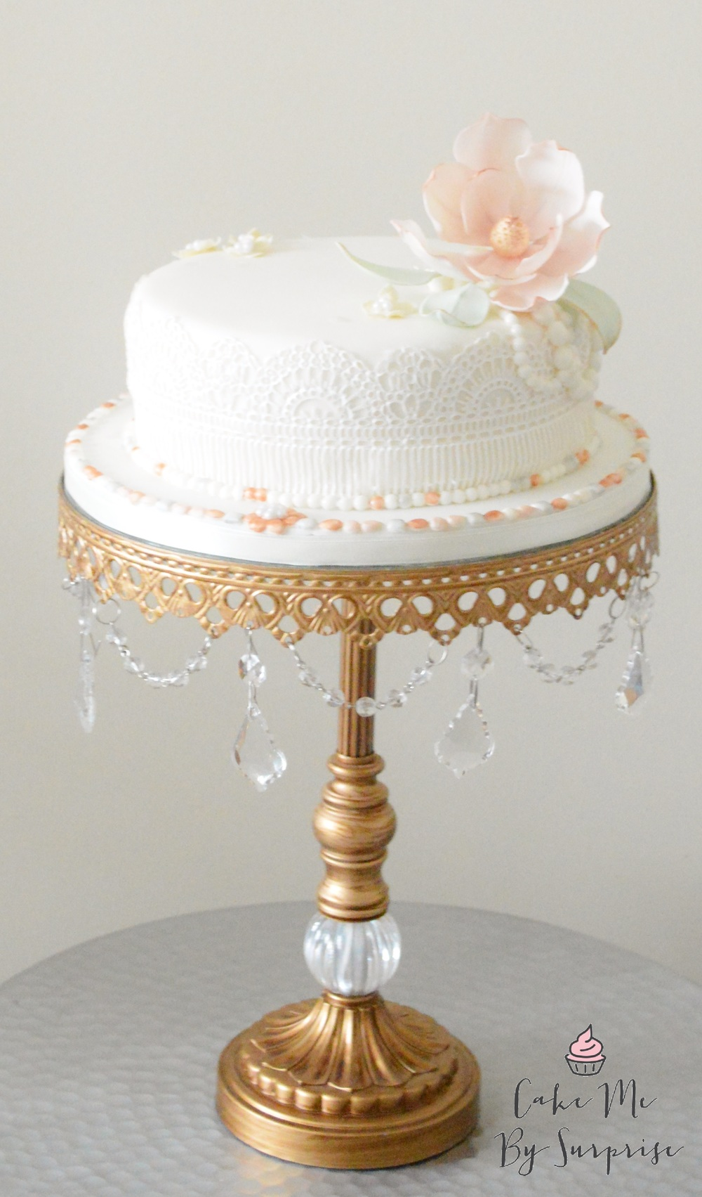 1920s Vintage Wedding   Perfect for an intimate wedding, a small serving vintage inspired wedding cake complete with pearls,handcrafted sugar magnolia and dressed with sugar paste beading and jewelry. This design can be adapted into a a tiered cake to achieve a real 'Wow!' factor.