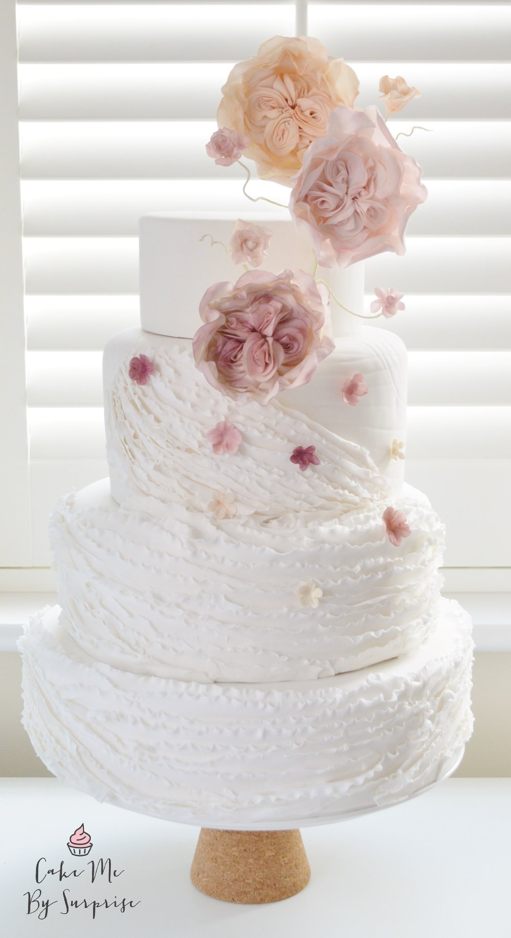 Spring Time Blossoms Delicate hand made ruffles elegantly wrap this cake, complete with soft falling blossoms in muted shades of plum, pink, peach and a shimmery ivory. Topped with trailing David Austin 'Cabbage Roses'  and wired fantasy flowers. Serves 100 £659
